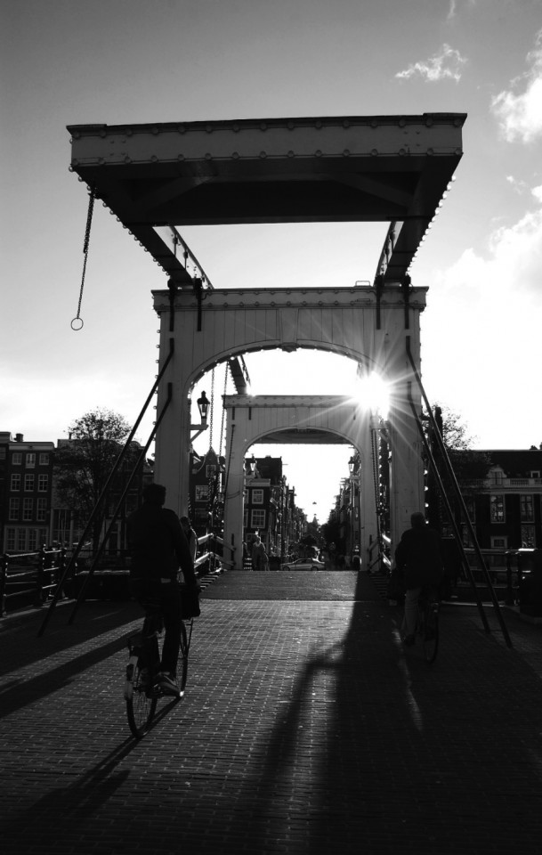 Where to take pictures in Amsterdam Magere Brug, the drawbridge over Amstel The Magere Brug or Skinny Bridge is a bridge over the river Amstel in the city centre of Amsterdam. This bridge connects the banks of the river at Kerkstraat between Keizersgracht and Prinsengracht and it is the perfect spot for cool shots! The bridge is very charming. Its old style and white colors can give your shots a cool look. Besides, it is located over the Amstel River, so the view is quite good from both sides.