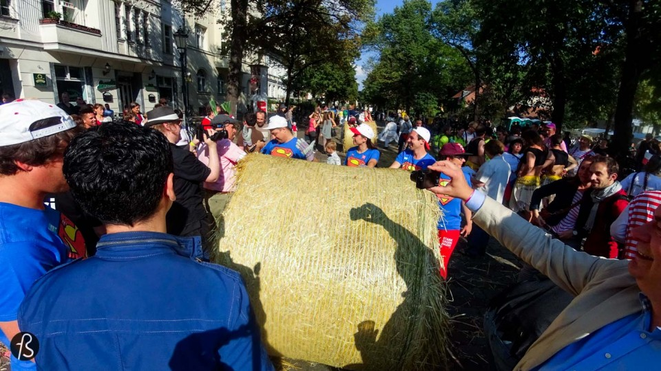 On September 12, 2015, we were in the middle of Rixdorf to see what could be only described as something really weird. Weird because we never imagined to see groups of people running around huge straw bale rolls on the streets of the German capital. But it happened in front of us and it was so cool we had to write about it here. But, before we say anything, we have to explain to you why this exists in the streets of Old Neukölln.