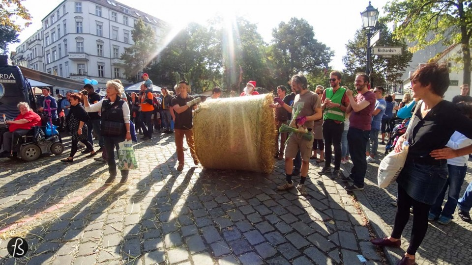 On September 12, 2015, we were in the middle of Rixdorf to see what could be only described as something really weird. Weird because we never imagined to see groups of people running around huge straw bale rolls on the streets of the German capital. But it happened in front of us and it was so cool we had to write about it here. But, before we say anything, we have to explain to you why this exists in the streets of Old Neukölln. This is Popraci.