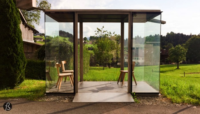 The bus stop designed by Smiljan Radic was the first one we saw while we drove around Krumbach with a map in hand. His design is a simple glass box with a black concrete ceiling with a wooden bird house attached to it. His work might look simple but it has clear inspiration to the handcraft and traditions of Vorarlberg. The inside area has references to the house parlor that is common in this part of Austria. With this in mind, the architect transfers the intimacy of the living room to an exposed bus stop.