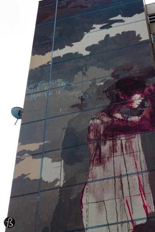 """The other mural I wanted to see was the infamous """"bloody refugee"""" mural that was receiving some controversy over its concept. This huge mural is the work of Spanish artist Borondo and depicts a girl in a white nightgown, covered in blood from the head down. She seems of the leaning against the building on which she is drawn. There is blood on the floor and there is more to it. On the other side of the building you can see a forest with a handcuffed, naked body pierced be arrows. Yeah, this sounds as gore as the moral itself as you can see on the pictures here."""