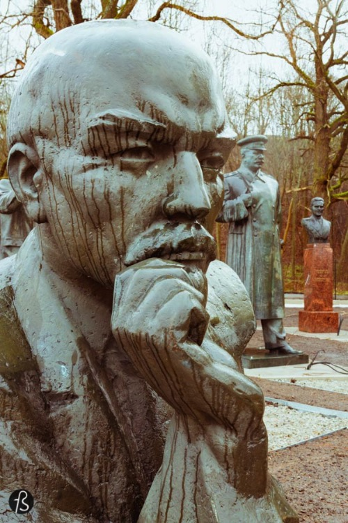 But still, Lenin's head was staring at me the entire rainy morning that I was there with Evo Terra, my partner in crime for the Soviet Statue Graveyard. And Lenin wasn't alone there. There were, at least, four of his heads there. Some of them are still attached to a body. Some are not. Most of them were made of steel but there was even a marble one there. Behind you can see some of his former comrades. Trotsky shows his face there without his hand. Stalin is also there and it's weird to see him there. They're surrounded by other communist statues, with faces that I can't recognize and without its official name tags. Maybe some of you reading this can but I can't. Sorry.