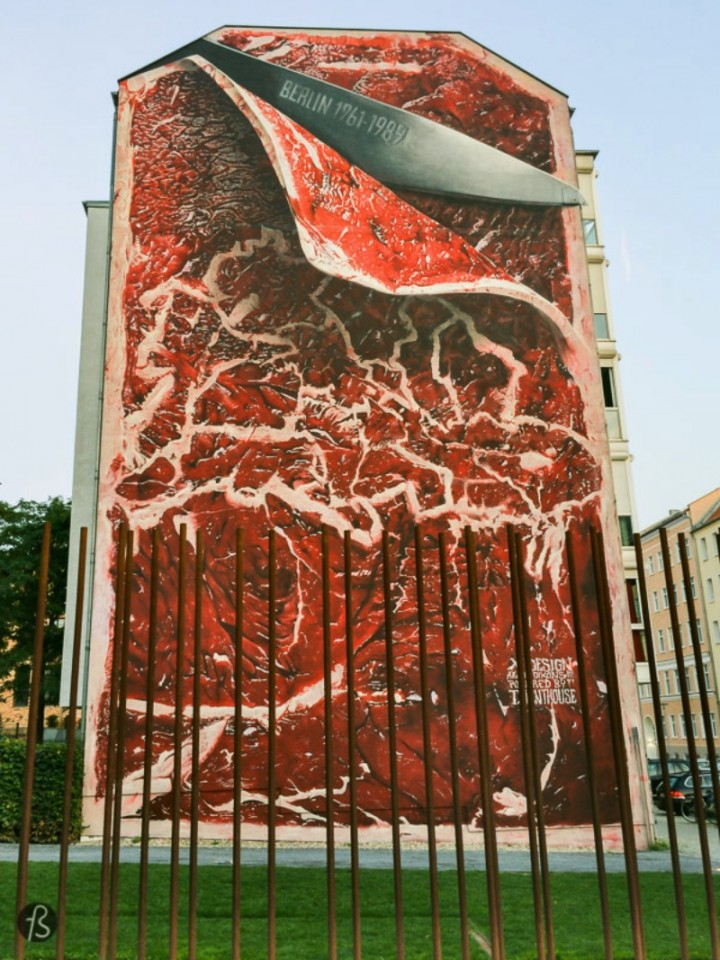 If you are a walk along where the Berlin Wall used to be around Bernauer Strasse, you will see a meat mural that might be our favorite street art piece in Berlin. This enormous painting shows the side of buildings being cut by a large knife with the shape of the city being represented in some white tissue. For us, this shows how the Berlin Wall was a scar running along the city.