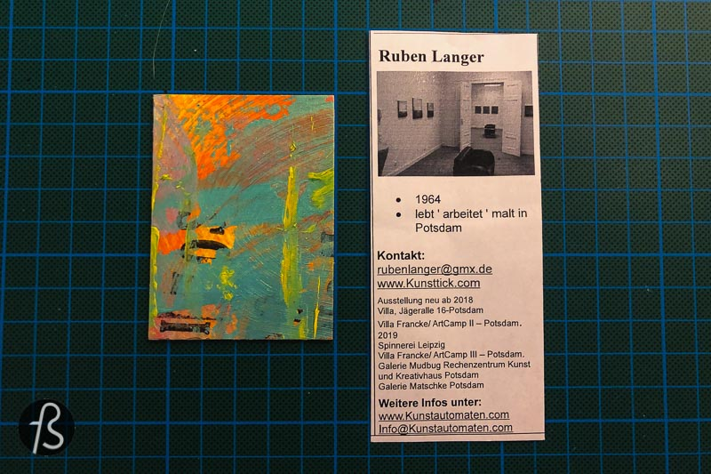 Once I saw it, I knew that I needed to buy a small piece of art from this small vending machine. Four euros later and there I was, holding a small paper box. Inside, I found a piece of paper explaining the artwork from Ruben Langer and the article itself. This abstract artwork is already hanging on my wall. My experience with the Kunstautomat was such a positive one that I needed to share with people.