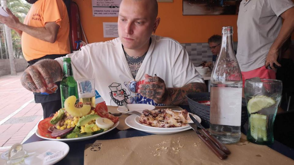 tattoos by mariano eating calamaris at restaurant nuevo gran playa