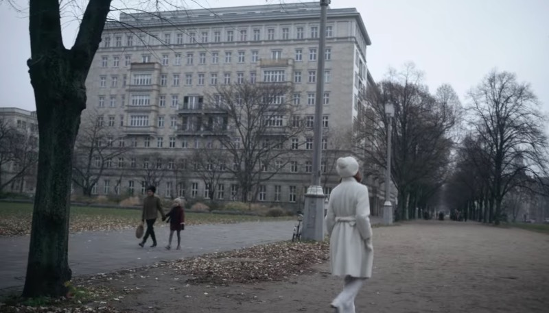 Everything happens around the Rosengarten on Karl-Marx-Allee. Beth walks away from a car and goes through the garden. She turns between some trees and sees the chess players. As you can see in the pictures we took, it looks almost the same as in the series.